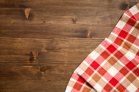 Checkered napkin at right bottom corner of wooden background top view