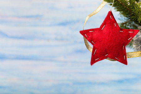 star ornament: Handmade red felt star hanging on fir-tree branch at right top corner of light blue background Stock Photo