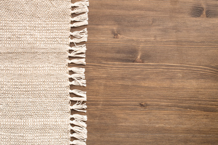 Handmade tablecloth at left side of wooden background