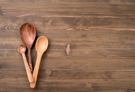 Three wooden spoons at left side of wooden table background Imagens