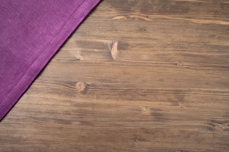 Purple  napkin from left top corner wooden table top view