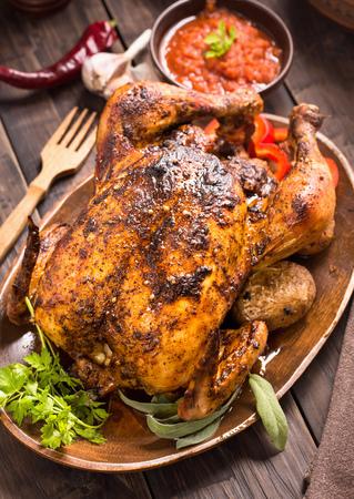 Gegrilde kip met groenten en greens op houten plaat