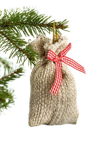 Christmas small gift bag decoration hanging on fir-tree branch isolated on white