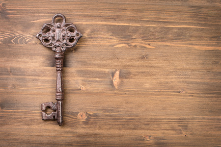 vintage objects: Old vintage key from left side of wooden background top view