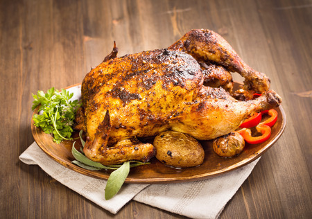 Grilled chicken with vegetables on wooden plate