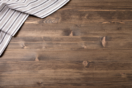 Striped kitchen towel from left top corner of wooden table top view. Food background