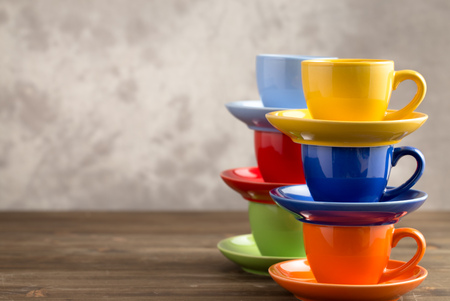 teacup: Two stacks multicolored cups on table from right side of gray background