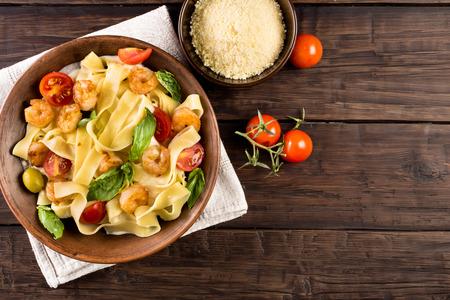 Fettuccine Pasta mit Garnelen, Tomaten und Basilikum auf alten Holztisch Draufsicht. Rustikaler Stil
