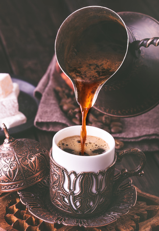 Pouring turkish coffee into traditional embossed metal cup.Toned Standard-Bild