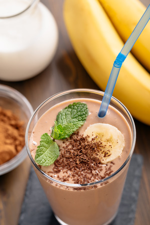 Glass of chocolate banana smoothie with straw top view Stock Photo