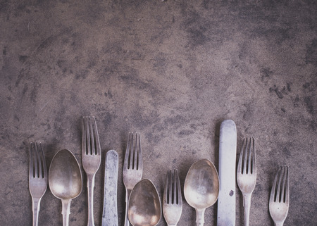 grunge silverware: Vintage silverware from bottom side of grunge background top view matte color