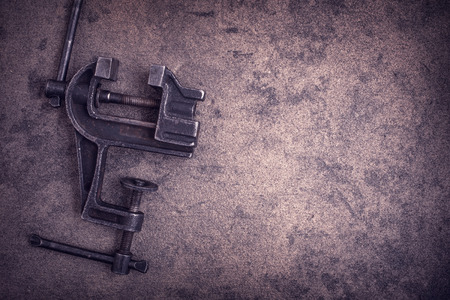 heavy metal: Old rusty vise tool on grunge metal surface with copy space.Toned