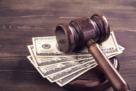 Gavel and some dollars banknotes.Auction bidding, judicial system corruption concept.Toned