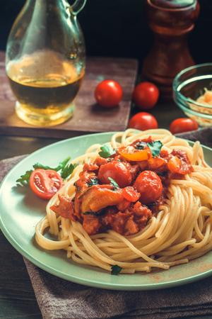 나무 테이블에 토마토 소스와 스파게티 파스타입니다.