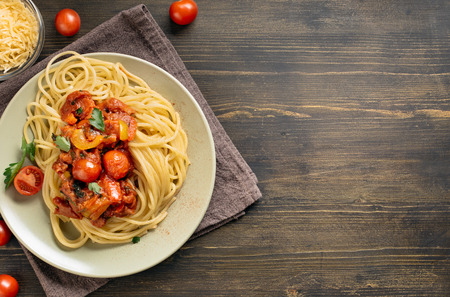 spaghetti dinner: Spaghetti pasta with tomato sauce on wooden table. Top view with copy space Stock Photo