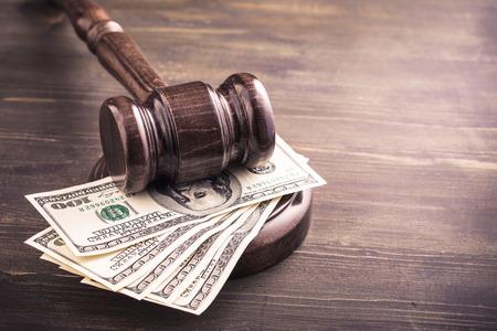 관행과 나무 테이블에 몇 달러 지폐. 경매 입찰, 사법 시스템 부패 개념입니다.