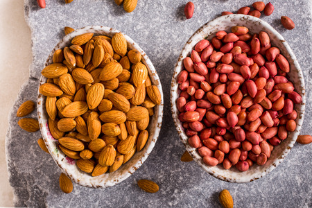 shelled: Bowls of shelled peanuts and almonds on stone background top view