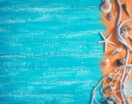 caracolas de mar: conchas de mar con red y la cuerda desde el borde derecho de la madera de fondo azul