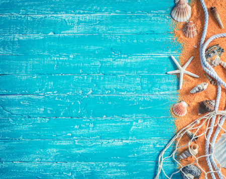shells: Sea shells with net and rope from right border of  blue wood background Stock Photo