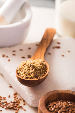colon cleansing: Flax seeds ground in spoon closeup Stock Photo