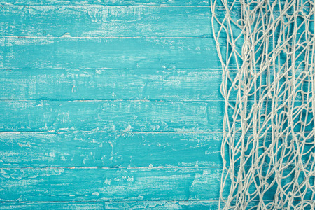 Fishing net from right side of old turquoise painted board background with copy space
