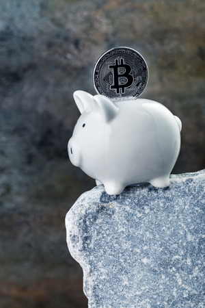 financial cliff: Piggy bank with bitcoin on the edge of stone cliff. Loss of savings concept Stock Photo