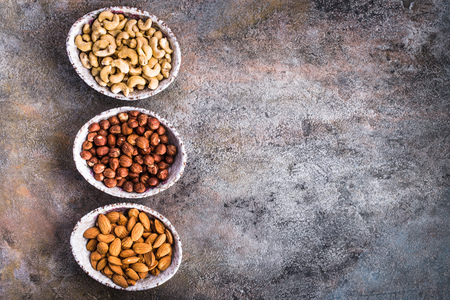 shelled: Top view of shelled hazelnuts, cashew and almonds bowls on rusty old background  with copy space Stock Photo