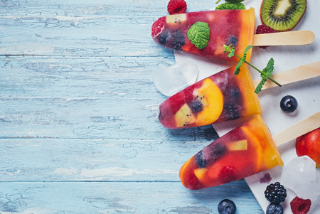 fruit: Homemade fresh berry and fruit ice pop on cyan wooden background top view with copy space