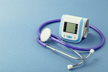 Stethoscope and wrist blood pressure monitor on blue background with copy space
