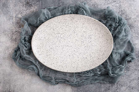 Empty oval plate with gauze on concrete