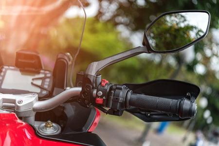 Motorcycle handlebar with button control  and mirror, selective focus.