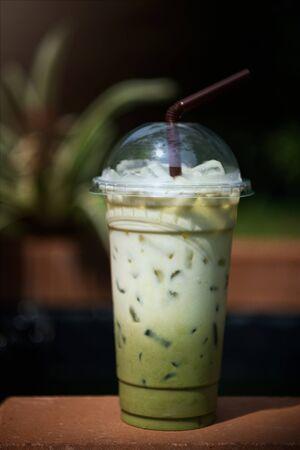 Iced matcha green tea latte on garden background.
