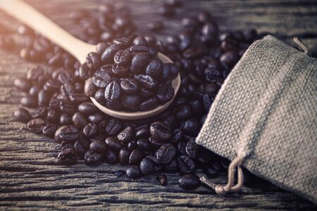 Coffee bean in spoon and bag on wood background