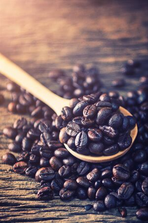 Close up Coffee bean in spoon on wood background 写真素材