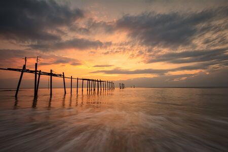 Beautiful of Old bridge and waves on sea at during sunset time Stock Photo