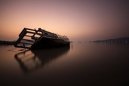 Fishing boat capsized on the beach in sunrise, image filter effect. Stock Photo
