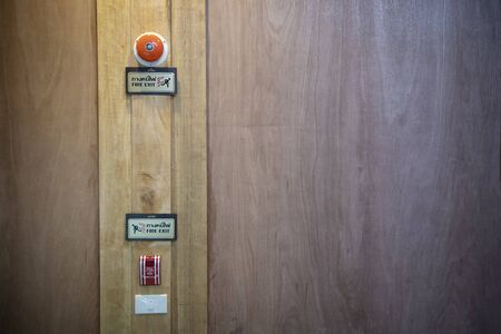 Fire exit sign and Fire alarm button security point on wood wall.