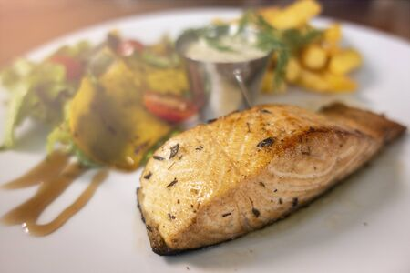 Grilled salmon salad with vegetables on white plate, selective focus. Stock Photo