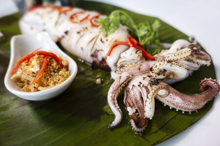 grilled squid with  sauce on banana leaf and on white plate ,selective focus.