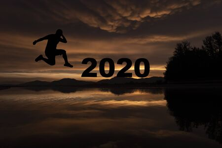 Silhouette Young man jumping to change 2019 between the 2020, New year concept. Stock Photo