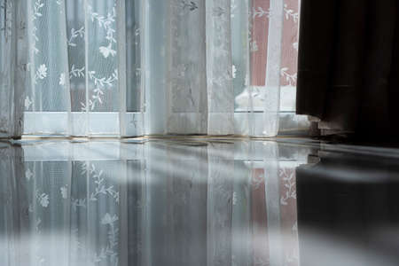 White lace curtain in the afternoon form a soft shadow on the floor