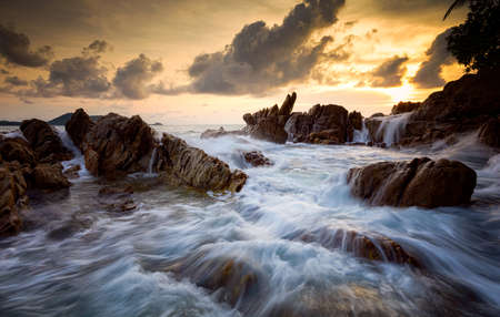 Seascape with rock in sunset scenery background, Seascape during storm and sunrise, Long exposure image of Dramatic sky.