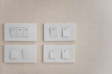 White lighting switchs on concrete wall, on and off