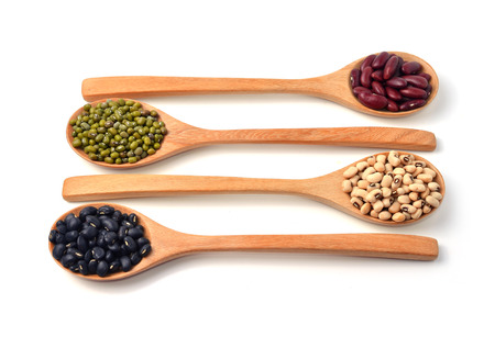 Green beans, black beans, red beans in wooden spoon, white background photo