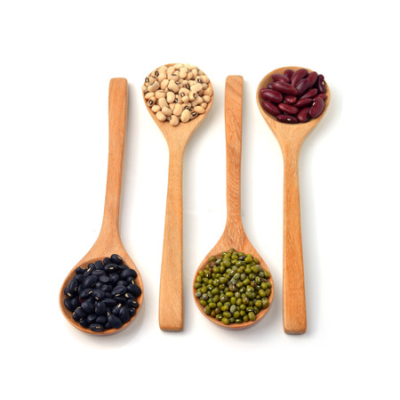 Green beans, black beans, red beans in wooden spoon, white background