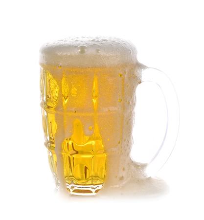 Overflowing beer glass on white background
