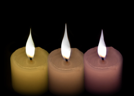 kwanzaa: Three white candles green and purple on a black background.