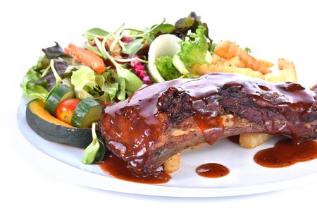 sauce dish: Rib steak served with salad on white background