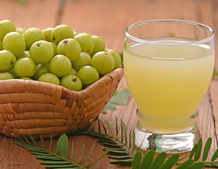 Indian gooseberry  juice on the wooden floor Stok Fotoğraf