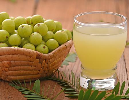 Indian gooseberry  juice on the wooden floor Standard-Bild